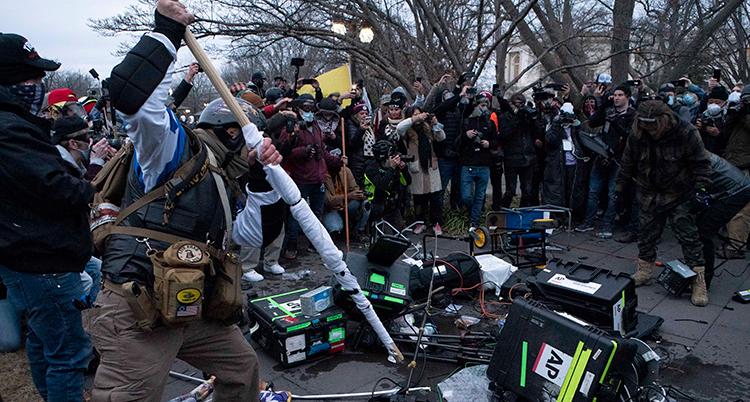Trasiga kameror ligger på marken. Runt dem står människor.