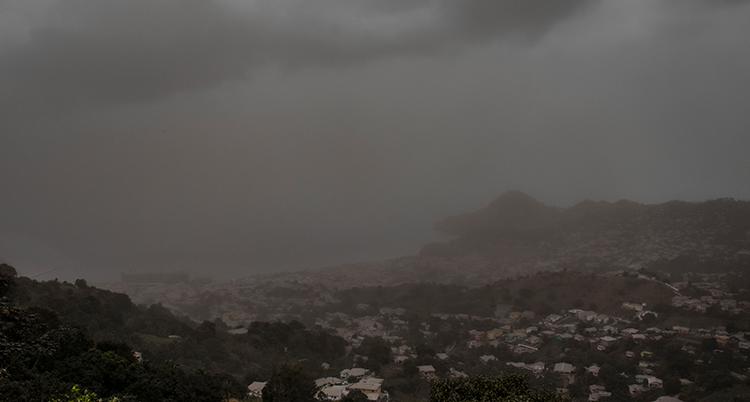 bilden ser nästan svartvit ut på grund av att askan gör luften grå. Bilden är tagen på avstånd mot bergen, allt ser ut att vara täckt i en grå dimma.