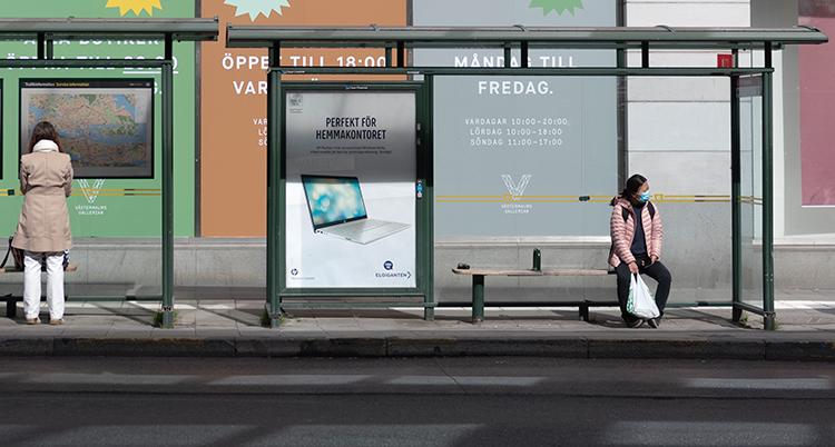 En busshållsplats. Två personer är långt ifrån varandra.