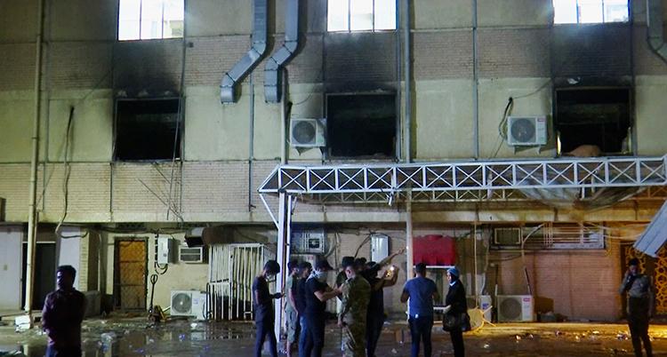 Flera människor står nedanför det förstörda sjukhuset.