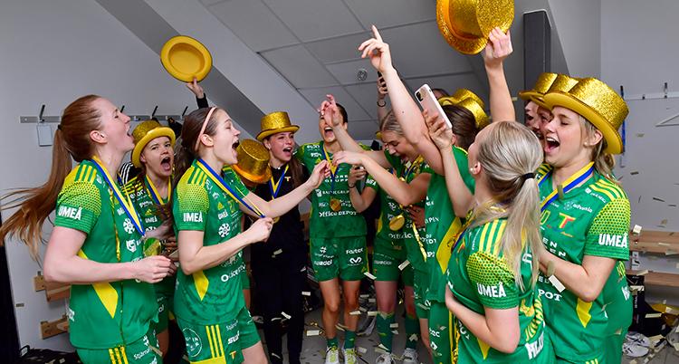 Månag spelare i gröna tröjor och hattar i guld jublar. De sträcker armarna i luften och det verkar som de sjunger.