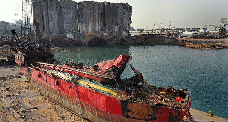 ett rostigt förstört skepp står på en trasig hamnkant. Bakom syns hamnen och hus som är förstörda.