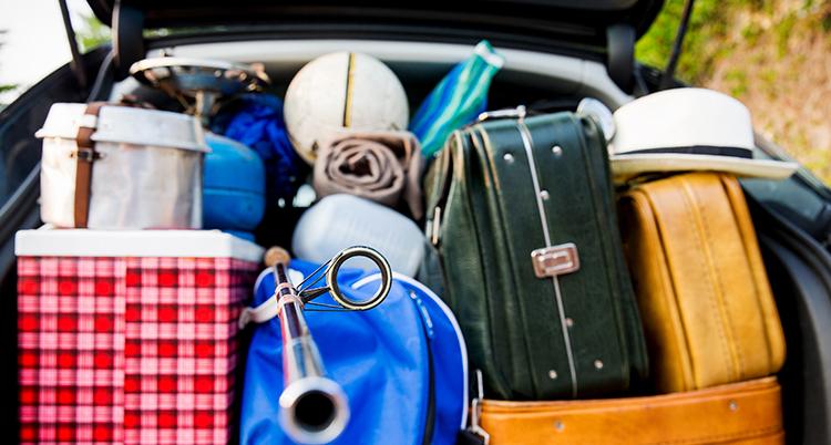 Bakluckan på en bil är full av resväskor.
