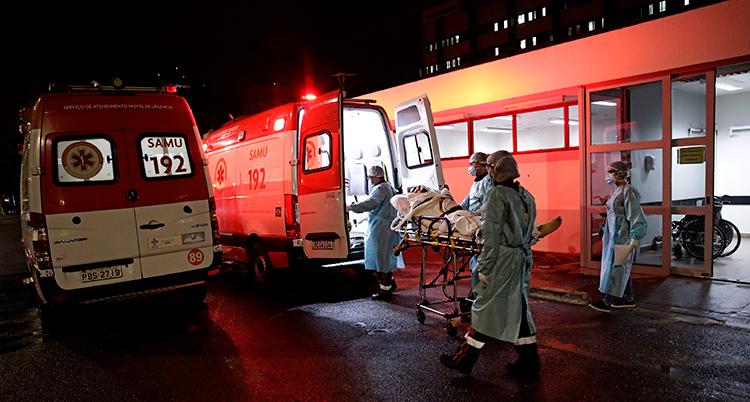 En röd ambulans har en öppna bakluckor. En människa bärs ut på en säng av flera personer. Det är mörkt ute.