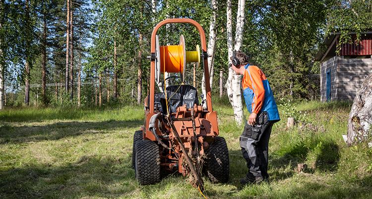 En orange maskin står ute på en äng. Den gräver i marken. En man står bredvid och tittar när den arbetar.