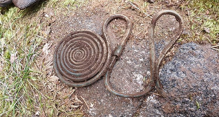 Ett spänne av brons. Det är en platt spiral och en slags krok går ut från den.