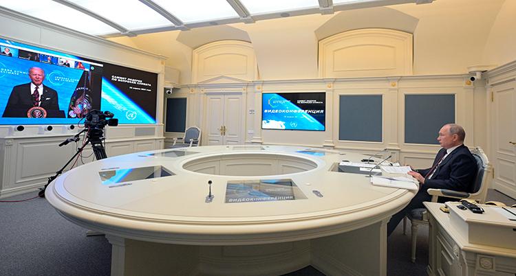 Ett stort rum med ett runt bord. Vid ena kanten sitter Putin. På andra ändan av rummet är en stor tv. Där syns Joe Biden. Hela rummet är vitt.