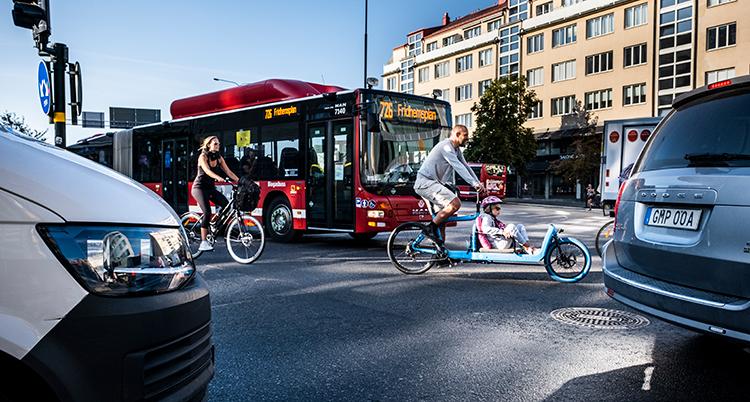 Trängsel på en gata. Ett par bilar är närmast kameran. Sedan kommert två cyklister framför en buss.