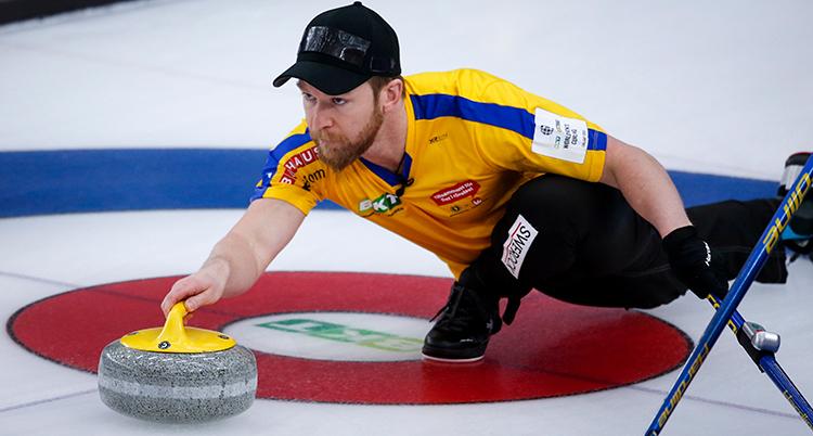 Edin i gul tröja och svart keps. Han nästan ligger ner på isen och har en sten med gult handtag i höger hand. Han är på väg att skicka iväg den.