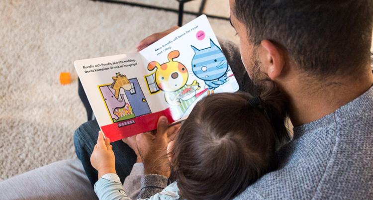 en pappa med sitt barn och en bok i knät