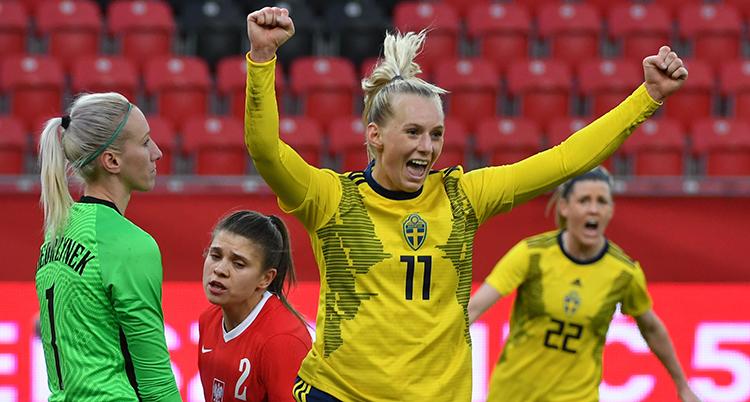 Stina Blackstenius sträcker armarna i luften och ser glad ut. Bredvid henne står Polens målvakt och ser uppgiven ut.
