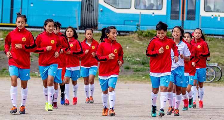 Fler än tio unga fotbollsspelare springar på en rad. De har röda jackor. De skrattar. De håller på att värma upp.