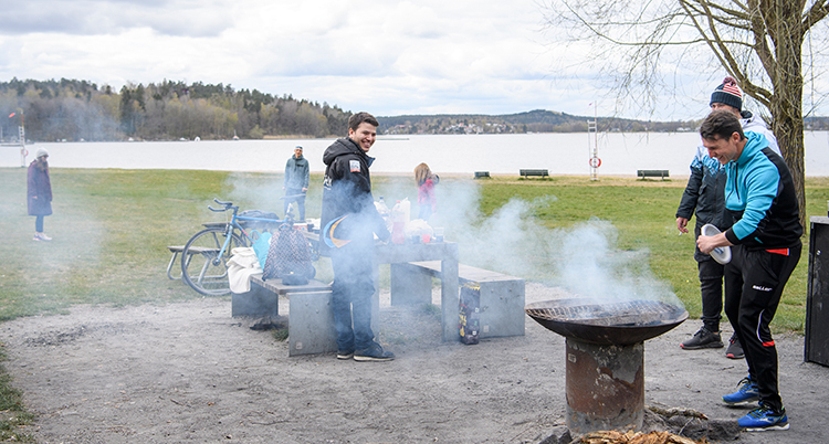 Några personer står vid en eld. Det ryker från elden. En sjö syns i bakgrunden.