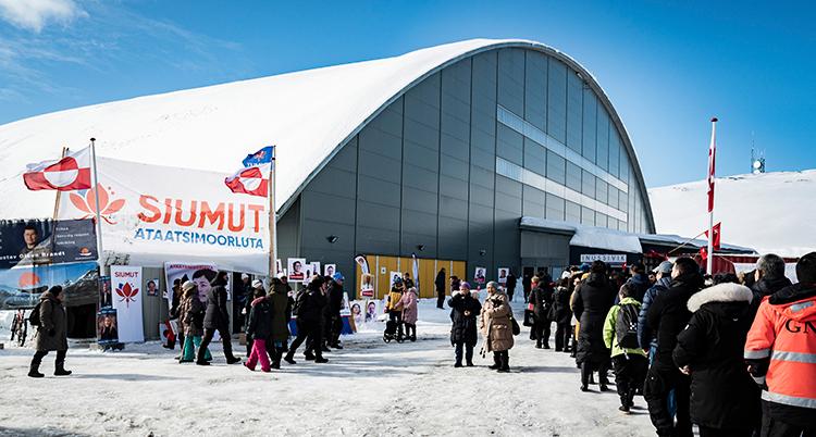 Människor står i en lång kö utomhus, framför en stor byggnad. Humlen är blå, marken täcks av snö. Alla har tjocka kläder på sig.