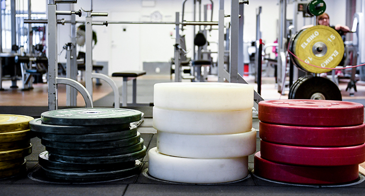 En bild på tre staplar med tyngder till tyngdlyftning. I bakgrunden syns maskiner i ett gym.