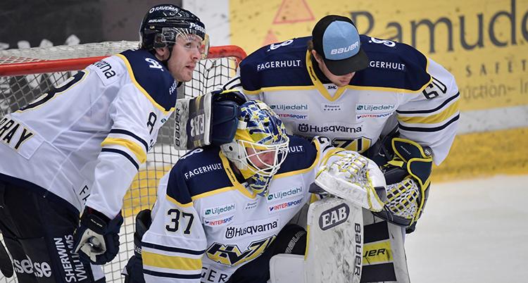 Två spelare står på varsin sida om målvakten. Två tittar ner i isen. Alla ser ledsna ut. En håller om målvakten.