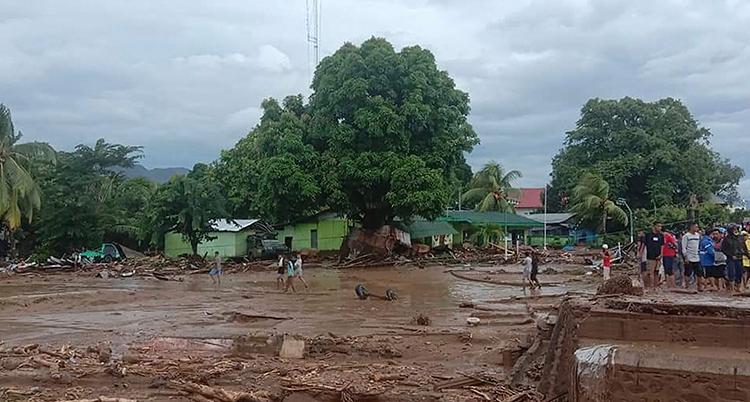 Marken är täckt av lera och vatten. Några människor syns på bilden.