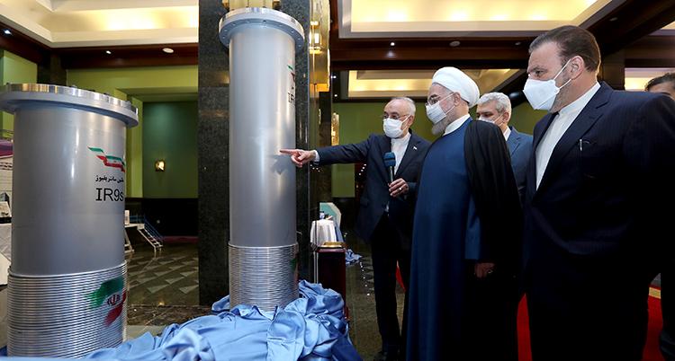 En man med turban oh några män i kostymer står framför några sorts rör. En av männen pekar på rören.