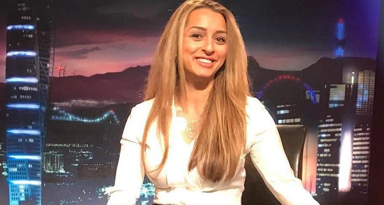 Hon har ljust hår och ler och tittar rakt in i kameran i en tv-studio