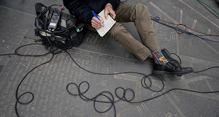 en person sitter på marken och skriver i ett block. Vi ser bara benen och händerna. Vid sidan ligger en väska med en inspelningsapparat och en lång sladd över marken.
