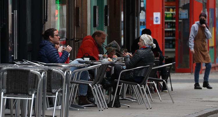 Några människor sitter vid ett bord på ett kafé. De sitter utomhus.