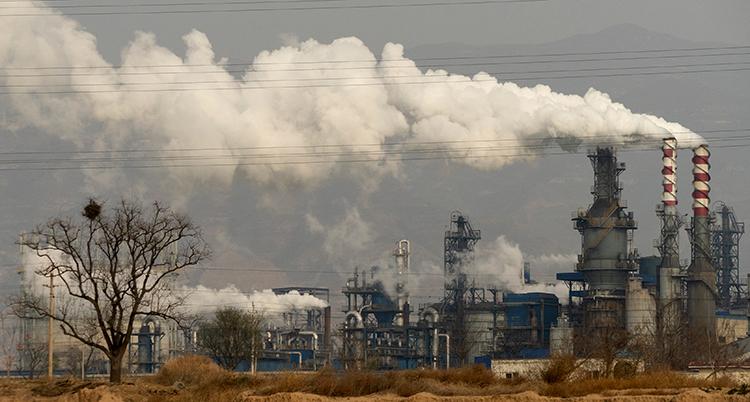 En fabrik med stora skorstenar som det kommer tjock vit rög igenom.
