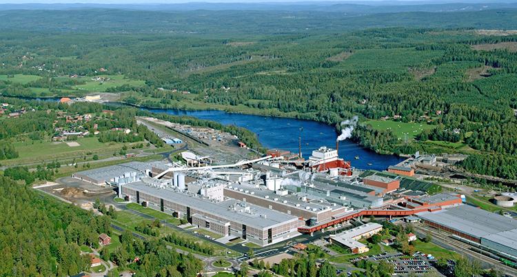 En stor fabrik ligger mitt i ett grönt skogslandskap, intill ett blått vatten.