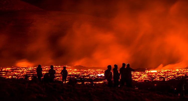 Rödaktig glödande lava syns på marken, i himlen är det rödaktig rök. Allt annat är svart och siluetter av människor syns i förgrunden.