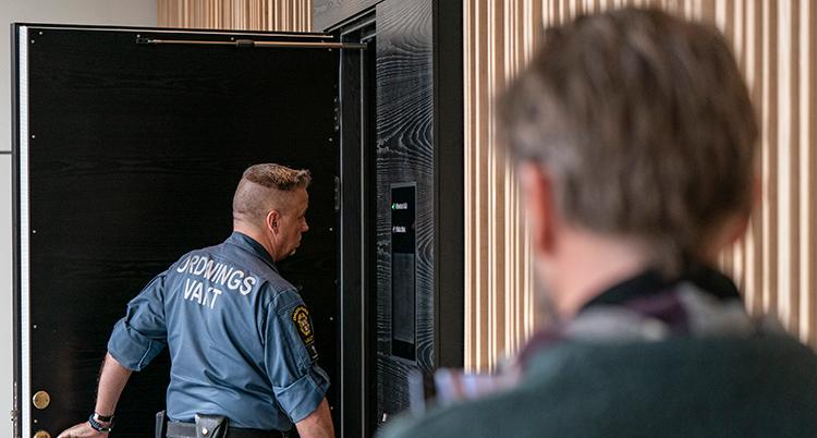 En ordningsvakt stänger en dörr i tingsrätten.