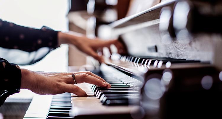 Händer spelar på orgelns svarta och vita tangenter