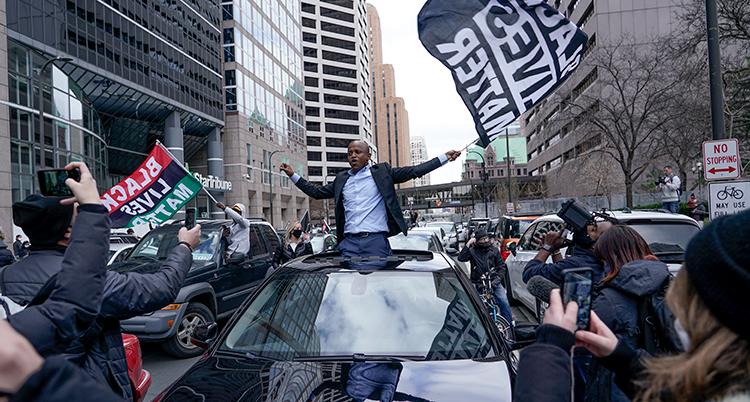 En man sitter i en taklucka på en bil. Han sväner med en svart-vit flagga och sträcker upp armarna. Runt bilen står många människor och tar bilder.