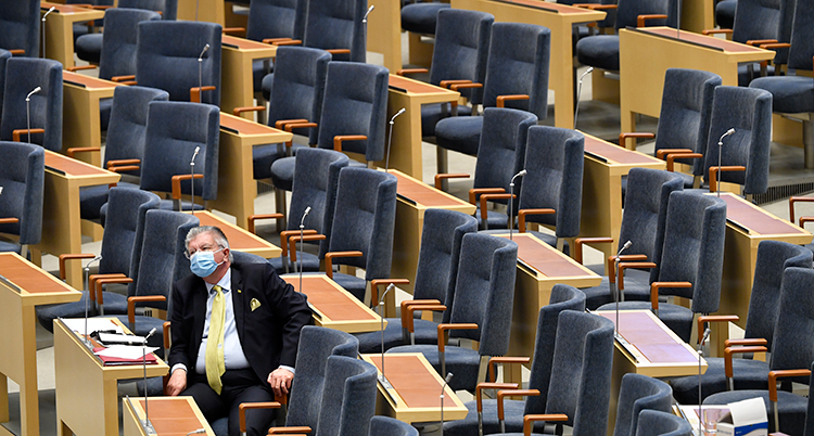 En ensam man sitter i riksdagens stora sal. Runt honom är många stolar tomma..