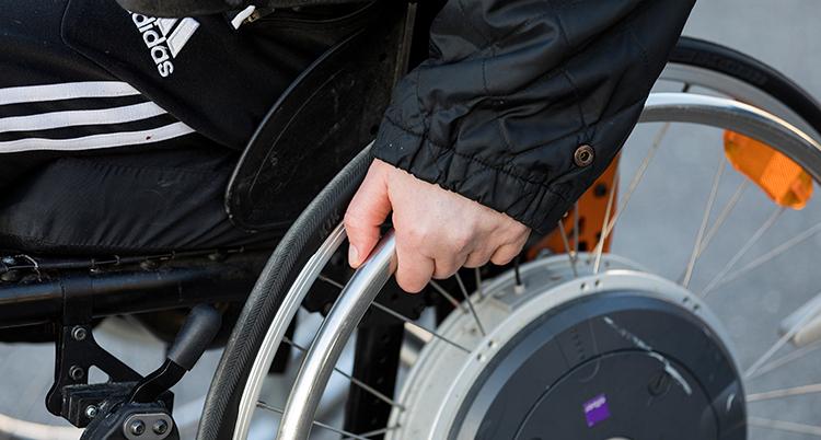 En nära bild på en hand som rullar hjulet på en rullstol.