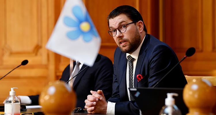 Åkesson sitter vid ett bord. Han ser allvarlig ut och har händerna knäppa på bordet framför sig. SDs flagga med en blåsippa står på bordet.