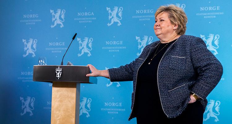 Solberg ser bister ut. Hon står vid en talarstol och håller handen på den.