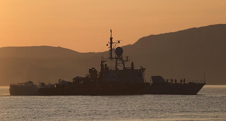 Det är solnedgång. En stor båt syns ute på havet.