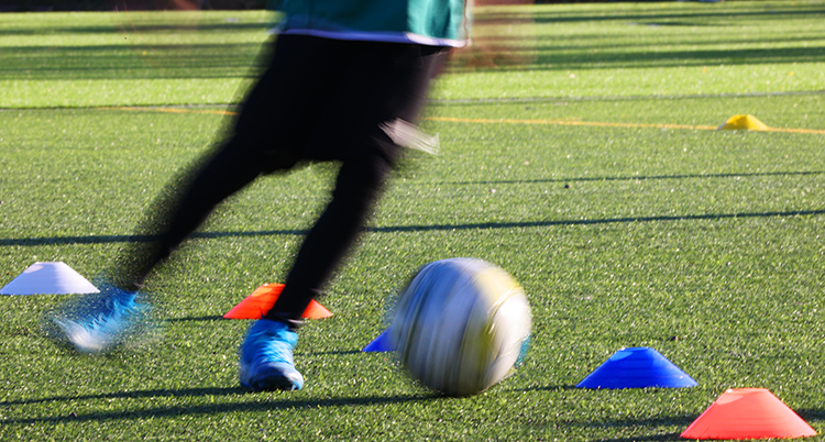 En ung person driver enn fotboll mellan små koner på en fotbollsplan. Bara benen och bollen syns.