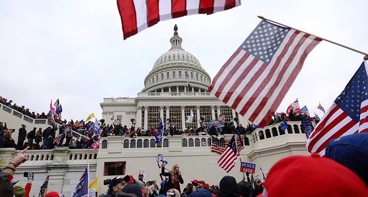 Många människor med USAs flaggor står utanför byggnaden.