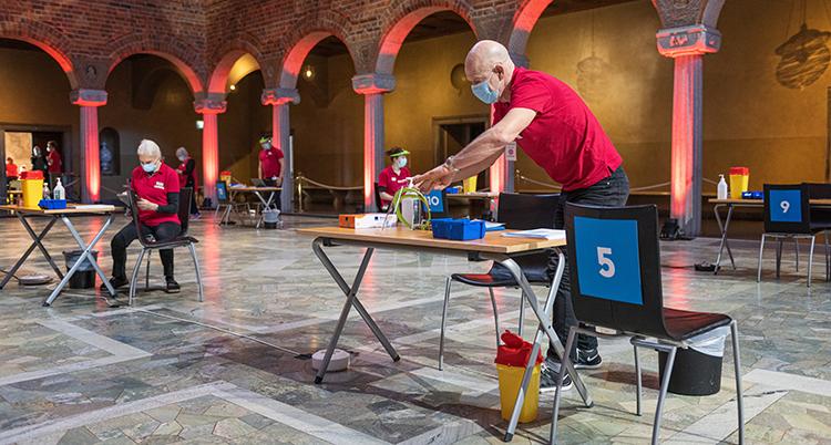 En man står vid ett bord i en stor sal med pelare i bakgrunden. Han håler på att plocka med sakerna på bordet. Bakom honom är människor vid likadana bord. Alla har röda tröjor.