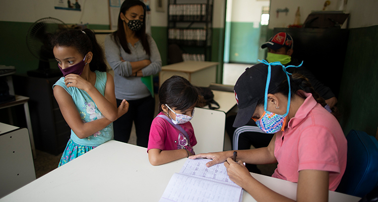 Barn står framför en bänk i ett klassrum och väntar på at få hjälp från den sittande läraren, som har munskydd