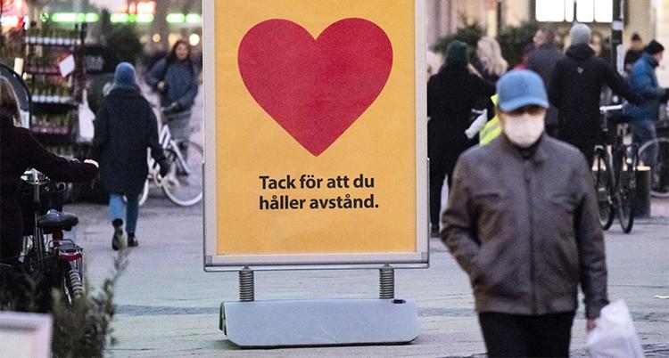 En stor skylt som säger: Tack för att du håller avstånd. En människa med munskydd går bredvid på gatan.