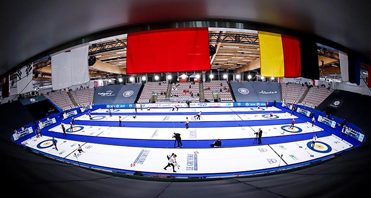 Bilden visar en stor hall för curling. Det är flera banor på is. Lag spelar matcher på de olika banorna.