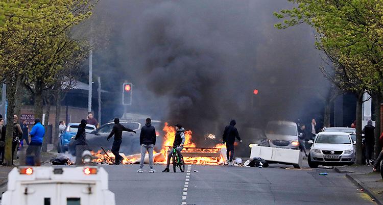 En gata i staden Belfast. Det är något som brinner på en gata. Flera personer är vid elden. Poliser är också där.