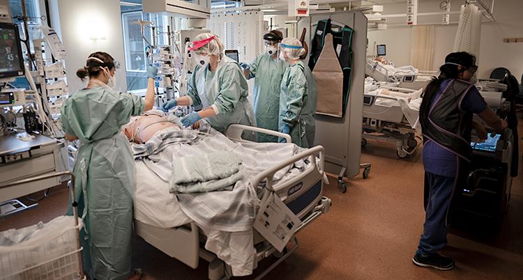 Från ett sjukhus. En person ligger på en säng. Personens ansikte är dolt. Personal ger vård. De har skyddskläder och skydd för ansiktet.