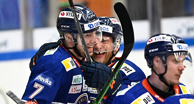 Från en match i ishockey. Tre spelare firar ett mål tillsammans. De är glada. De har hjälmar, klubbor och blå dräkter.