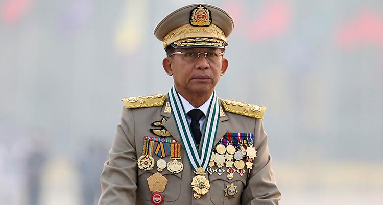 En man som är klädd i en kostym för militärer. Han har en militärhatt på huvudet. Han har massor av medaljer på kavajen.
