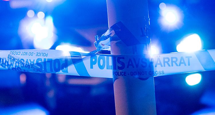 Det är utomhus. Det är mörkt. Poliser har satt upp avspärrningsband runt en lyktstolpe. I bakgrunden syns blåljus från en polisbil.