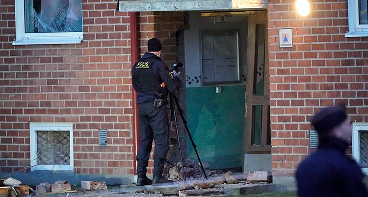 Poliser undersöker en av explosionerna. Fasaden på ett tegelhus ser lite förstörd ut. Fönster krossade och lösa tegelstenar ligger på marken.