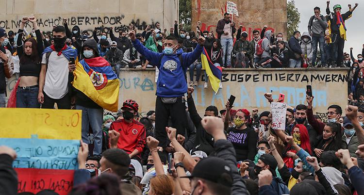 Människor har samlats utomhus för protest. Många sträcker upp näven i luften. En del har plakat.