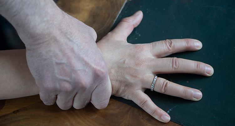 en hand från en person som ser ut att vara en man håller hårt om en hand som ser ut att tillhöra en kvinna. Den hand som blir fasthållen har utspärrade fingrar.